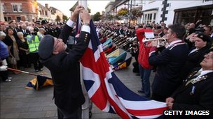 A standard bearer lowers the union jack in Wootton Bassett