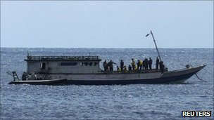 An Australian Navy boat comes alongside a boat carrying 50 asylum seekers after it arrived at Flying Fish Cove on Christmas Island, about 2,600 km (1,615 miles) north-west of Perth, 7 August 2011