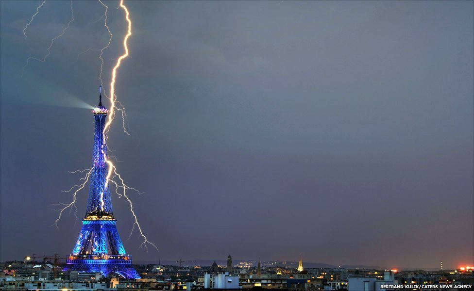 A lightning bolt appears to strike the iconic Eiffel Tower while the Paris landmark is seen illuminated in vibrant blue lights.