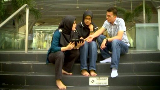 People sat on steps using smartphone religious apps