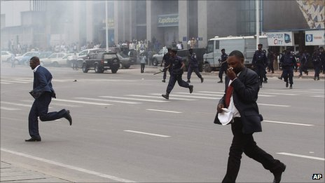 Opposition politician Honore Okundji, left, runs as police chase protesters during a demonstration in Kinshasa, DR Congo, 1 September 2011