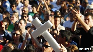 A man holds up a white cross during a protest against violence in Monterrey on 28 August 2011