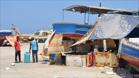 Migrant workers camp at a fishing port near Tripoli