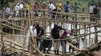 People crossing makeshift bridges