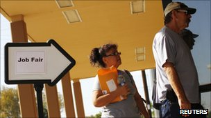 A man and woman enter a job fair in Phoenix, Arizona, on 30 August 2011