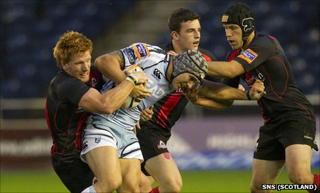 Cardiff's Tom James is tackled by three Edinburgh players