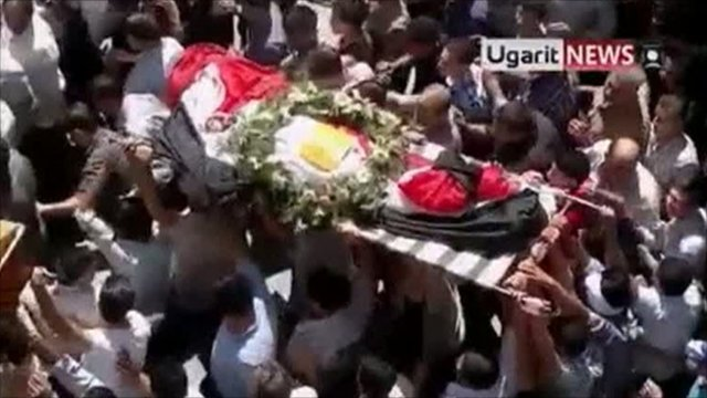 Protesters carry a coffin during funeral procession in Damascus