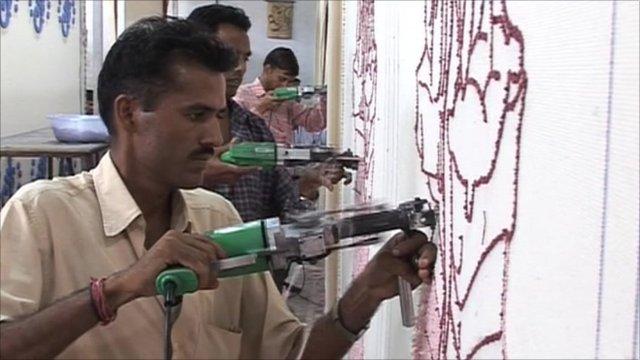 An Indian worker threads fabric onto a drape