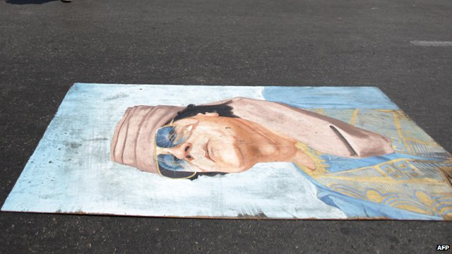 A portrait of Col Gaddafi lies on the street in Tripoli