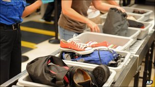 In this Aug. 3, 2011 photo, airline passengers retrieve their scanned belongings while going through the Transportation Security Administration security checkpoint at Hartsfield-Jackson Atlanta International Airport, in Atlanta.