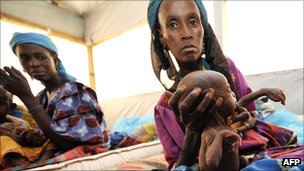 Woman holds her malnourished child ata nutritional rehabilitation centre in southern Niger during 2010 Sahel drought