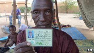 Silimane Albaka, a Tuareg from Niger who recently returned from fighting alongside Gaddafi loyalist forces in Libya, shows his Libyan army card as he sits in front of his house outside of Agadez on 2 September 20111