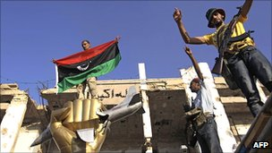 Libya rebel fighters celerbate around Col Muammar Gaddafi's monument to the 1986 US bombing after storming the dicator's Bab al-Aziziya compound