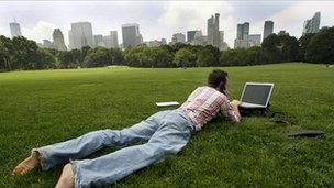 Man uses laptop in park with view of city in background
