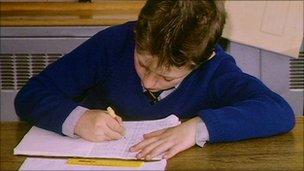 School boy writing in classroom