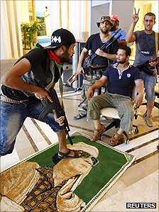A former rebel steps on a poster of Col Muammar Gaddafi while others pose for the camera at the Rixos Hotel in Tripoli