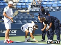 Andy Roddick, David Ferrer and Carlos Bernardes inspect a crack on Louis Armstrong Stadium