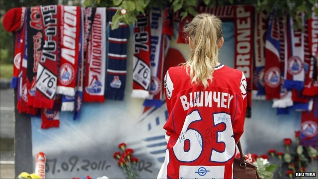 Woman in hockey shirt in front of wall covered in tributes to the team
