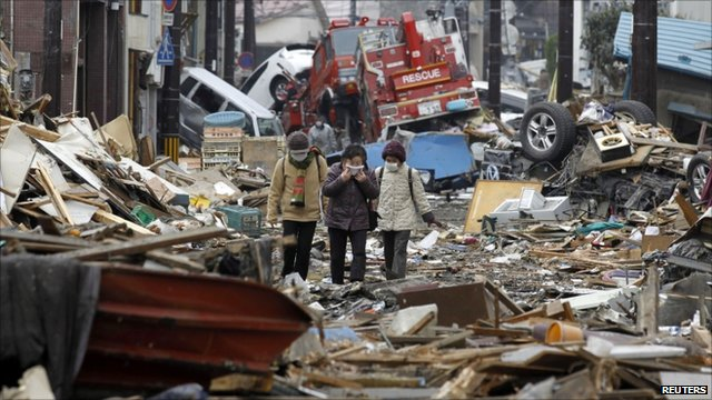 People walk through rubble after the tsunami in March
