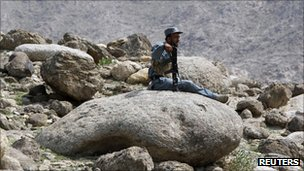 An Afghan policeman rests while patrolling with U.S. soldiers from Task Force Bronco, 3rd Squadron, 4th Cavalry, to search for arms cache, in a village in Nangarhar, Afghanistan September 8, 2011. 