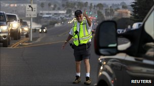 A volunteer community police officer directs traffic along the 101 highway following a power outage in Cardiff, California, September 8, 2011