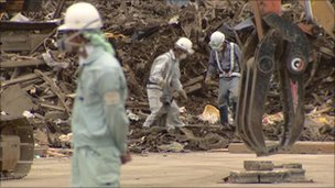 Men with mechanical shovels and diggers sift through the debris