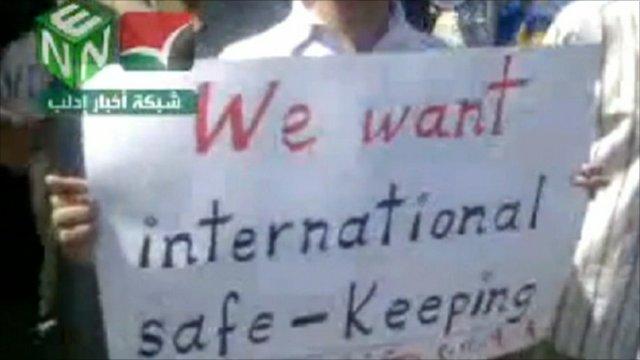 "Placard saying ""We want international safe-keeping"""