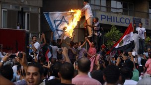 Protesters wave the Egyptian flag and set fire to a depiction of an Israeli one outside the Israeli embassy in Cairo.