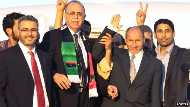 Mustafa Abdul Jalil, second from right, waves to supporters as he arrives at Mitiga airport in Tripoli