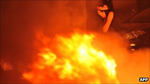 A woman passes a fire during protests  Thessaloniki, 10 September 