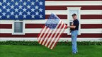 House painted with American flag and man waving an American flag. Photo: Robert Carley taken in Nebraska