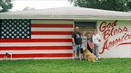 Family in front of house with an American flag and God Bless America written on it. Photo: Robert Carley, taken in Florida