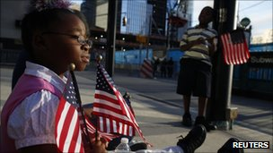 A little girl holds the US flag at Ground Zero