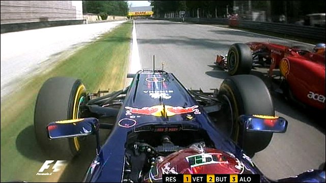 Sebastian Vettel takes to the grass to overtake Fernando Alonso