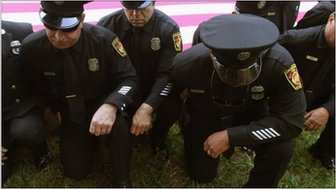 New York City Firefighters kneel in front of the US flag and mark a moment of silence on the 10th anniversary of 9/11