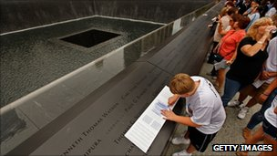A boy makes a rubbing of his father's name at the 9/11 memorial