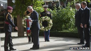 The Prince of Wales laying a wreaths at the memorial, watched by David Cameron (r) and Louis Susman