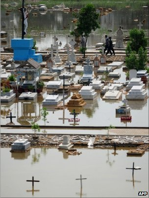 Pakistani people walk in a flooded grave yard after rain in Karachi on September 11, 2011