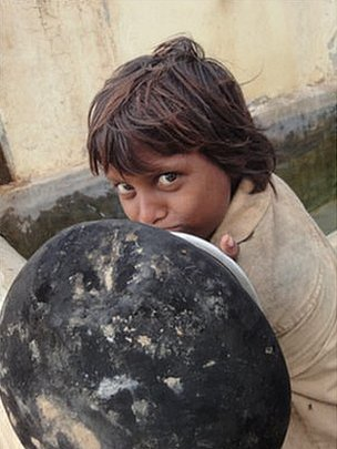 A child waits to fill his water jar from a communal tap