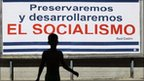 "Boy crosses a street near a billboard in Havana, saying ""we will preserve and develop socialism"" on 3 August, 2011."