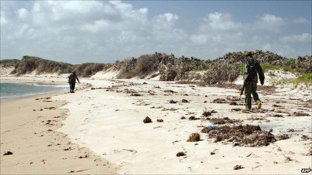 Armed police patrol a stretch of beach near Kiwayu Safari village, where British couple David and Judith Tebbutt were attacked
