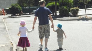 Man holding hands with two children