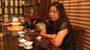 Cui Yunhua, owner of a tea shop in Dalian, with teacups