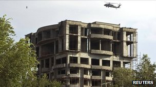 A Nato helicopter flies next to the building which the Taliban insurgents took over during an attack near the US embassy in Kabul