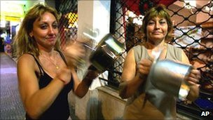 Two women bang pots and pans during a demonstration when Argentines turned off their lights in a nationwide blackout symbolising their discontent with the economic measures of the Argentine government in Buenos Aires