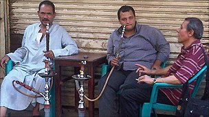 Men smoking shisha (water pipes) on a street in Cairo