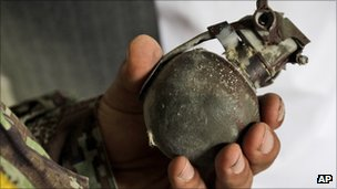 Police officer holds a grenade in the recaptured building in Kabul, Afghanistan (14 Sept 2011)