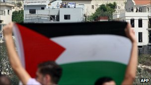 Palestinian flag held aloft near Jewish settlement in West Bank. 9 Sept 2011