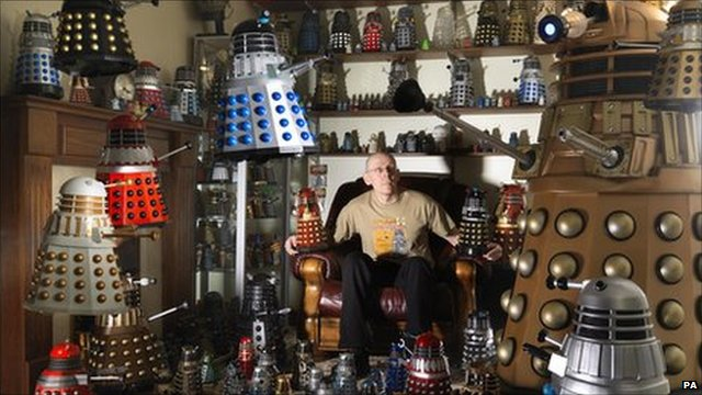 Rob Hull surrounded by his collection of Daleks