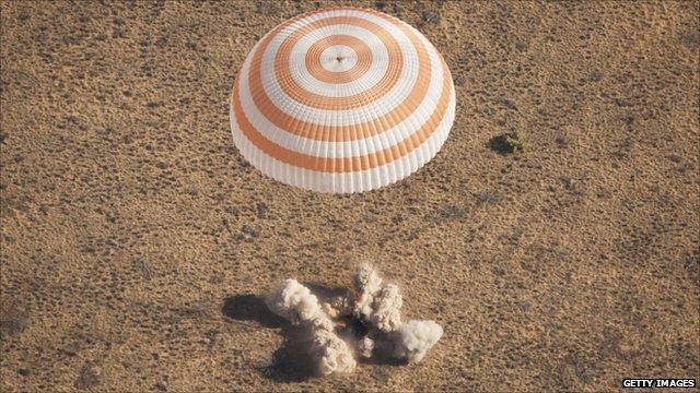 Parachute above plume of dust caused by Soyuz capsule landing in Kazakhstan
